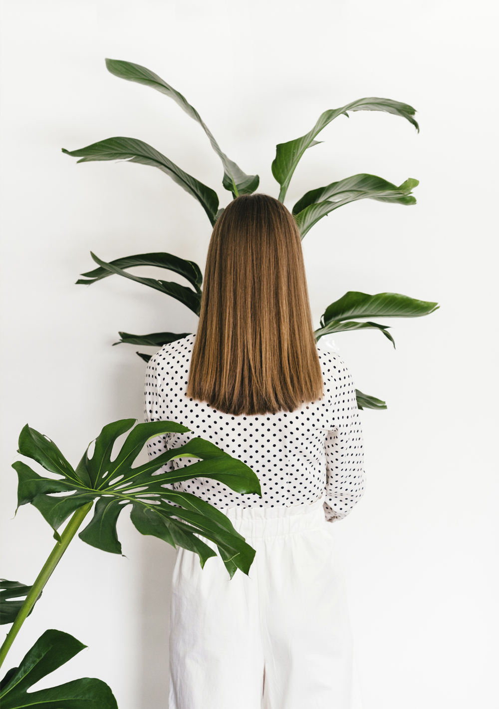 Woman from the back holding plant