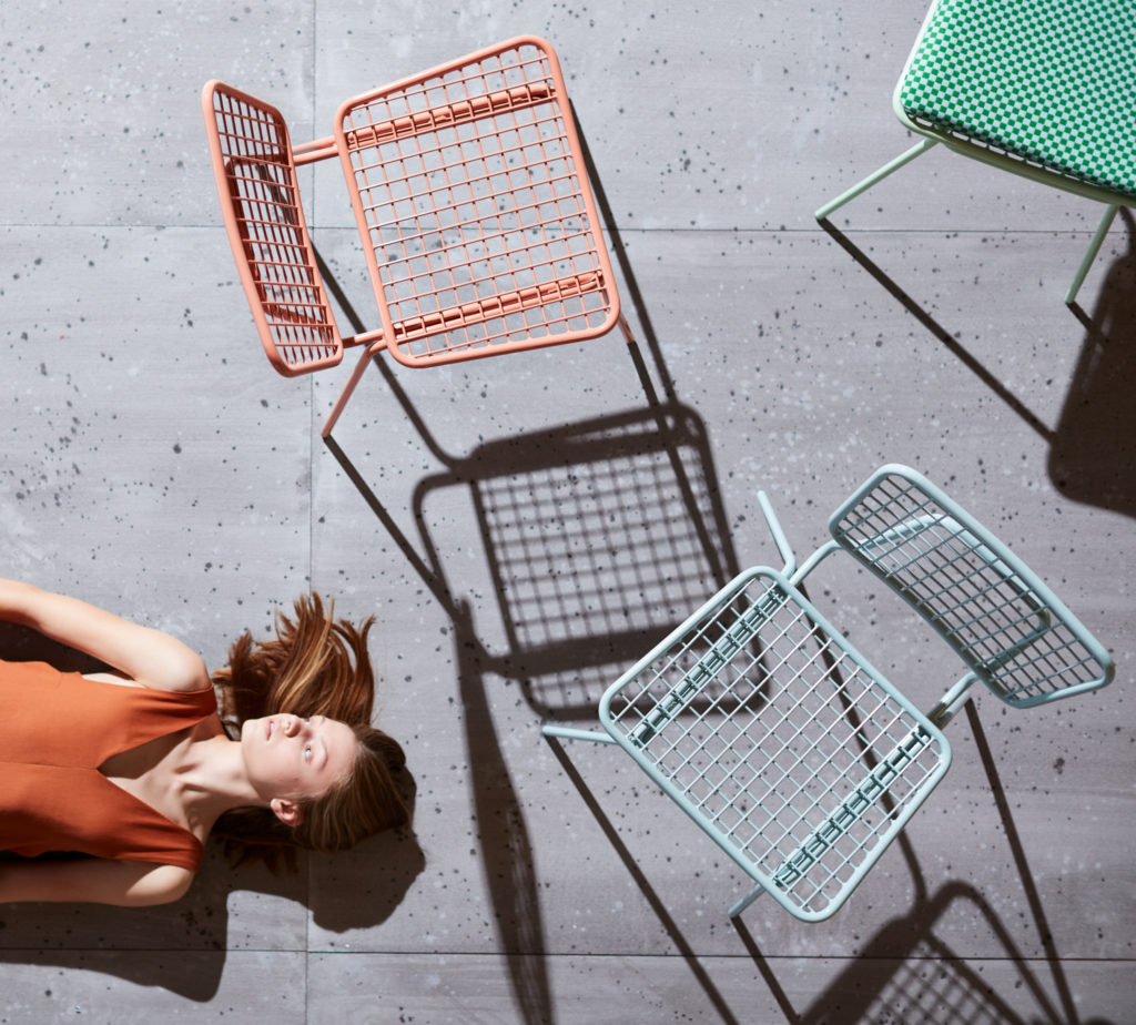 Outdoor furniture and woman lying on ground