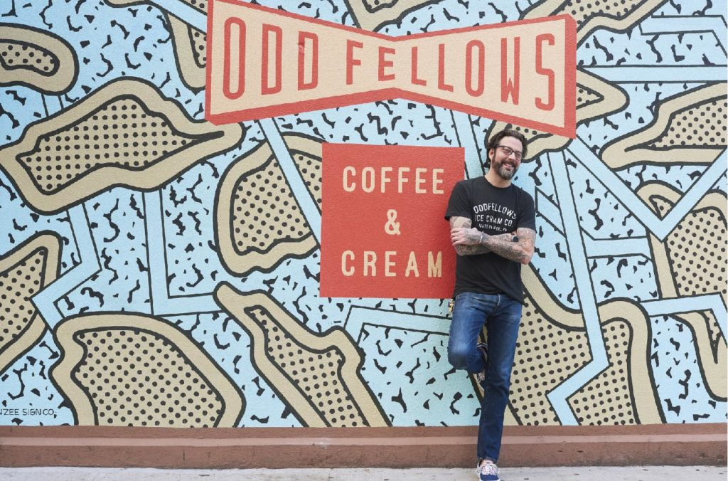 Sam Mason standing in front of OddFellows mural
